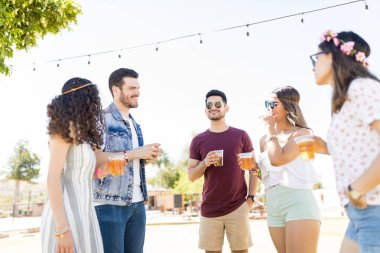 Young men and women talking while holding beer glasses at summer party