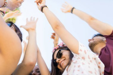Excited music fans dancing together at live concert during weekend