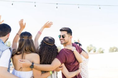 Happy young man having fun with friends in music concert during summer