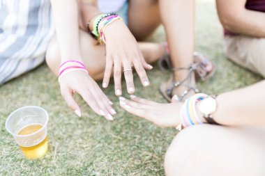 Cropped image of female friends matching painted nails while sitting on field during summer