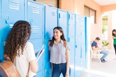 Teenage students gossiping while standing by lockers in campus