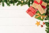 Pohled na několik vánočních dárků a garlandický rám s ozdoby a prostor pro kopírování na dřevěném stole