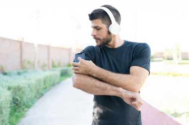 Sporty young man listening music through wireless headphones while working out in park