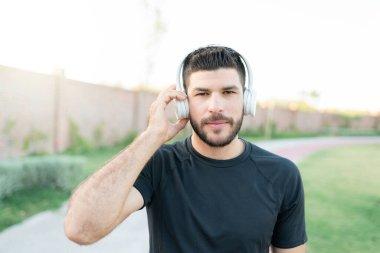 Sporty good looking Hispanic man listening music through headphones while exercising in park