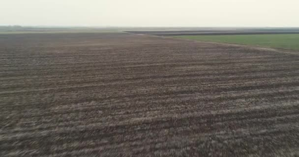 Camera flies back to reveal a film crew setting up a scene in the field. Winter, cloudy.
