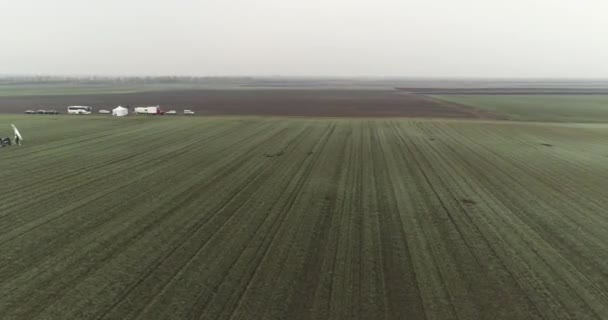 Camera flies left to reveal a film crew setting up a scene in the field. Winter, cloudy.