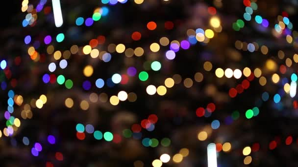 Blurred Christmas tree decorated with snow, gifts and colorful garland