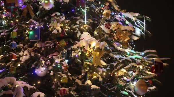 Detailní pohled na vánoční stromeček zdobený sníh, dárky a barevná girlanda