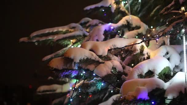 Closeup view of Christmas tree decorated with snow, gifts and colorful garland