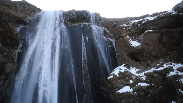 Krásná Seljalandsfoss na Islandu v zimě. Zmrazené krásný vodopád Seljalandsfoss pod světla východu slunce v zimě, odraz v řece. Seljalandsfoss se nachází v kraji na Islandu.