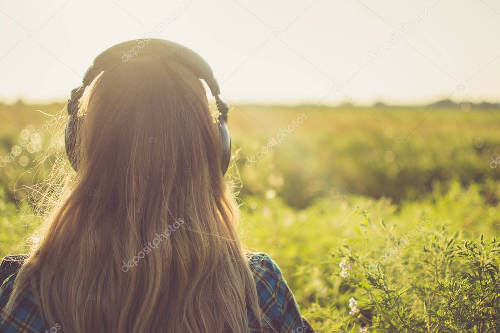 girl with headphones back view. looks into the distance with nature in the horizon.