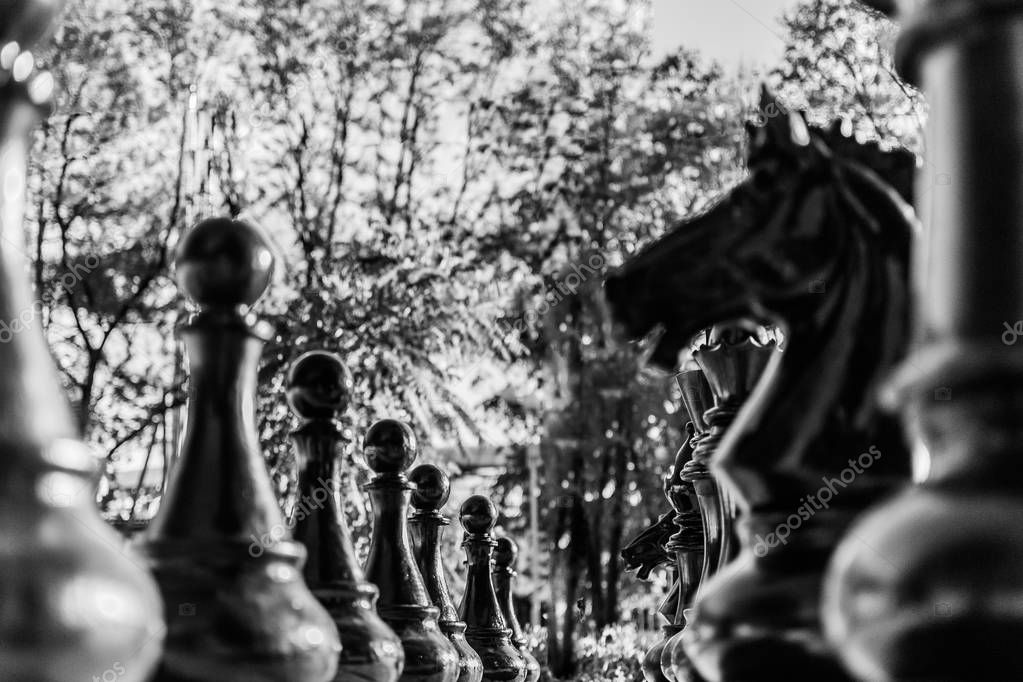 street chess pieces in monochrome. background. close up
