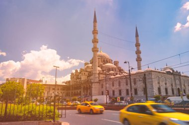 ISTANBUL, TURKEY JULY 5, 2014: Yeni Cami Ottoman imperial mosque located in the Eminn quarter of Istanbul, Turkey. Strait of Bosporus with ships in foreground and blue cloudy sky in background.