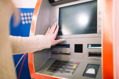 Young woman withdrawing money from credit card at ATM. Selective focus.