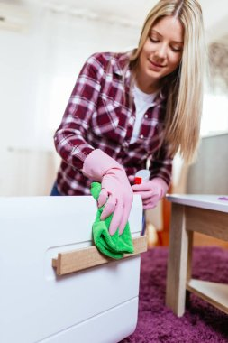 Beautiful young smiling woman cleaning house with microfiber cloth.