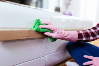 woman cleaning house with microfiber cloth