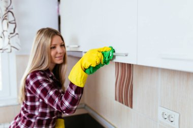 Beautiful young smiling woman cleaning house.