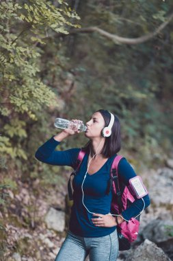 Young woman in a forest opening a bottle of fresh water during an autumn walk.