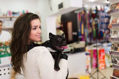 brunette woman with her French bulldog puppy in pet shop.