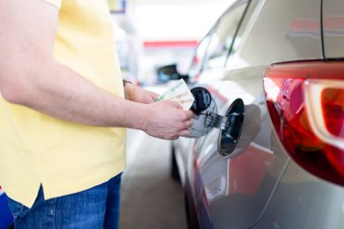 man filling gasoline fuel in car at gas station