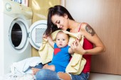 Mother and cute baby boy loading clothes into washing machine.