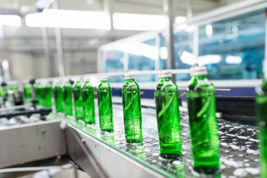 Bottling plant - Water bottling line for processing and bottling pure spring water into green glass bottles. Selective focus. stock vector