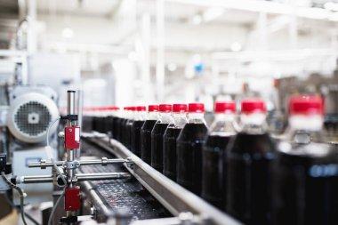 Bottling factory - Black juice bottling line for processing and bottling juice into bottles. Selective focus. stock vector