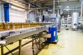Photo Bottling factory - Apple juice bottling line for processing and bottling juice into bottles. Selective focus.