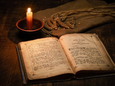 Eski kitap İncil'i Rusya ve eski Slav dilleri bir mum ve buğday keten kumaş üzerinde kulakları ışığında ahşap bir masa