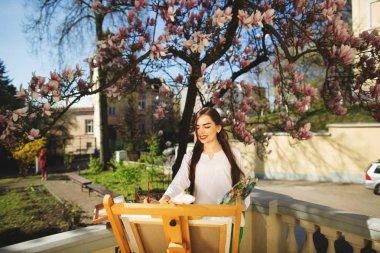 """Картина, постер, плакат, фотообои """"Молодая брюнетка женщина-художница, держащая в руках кисть и палитру. Рядом с ней дерево магнолии и различное художественное оборудование"""", артикул 270855212"""