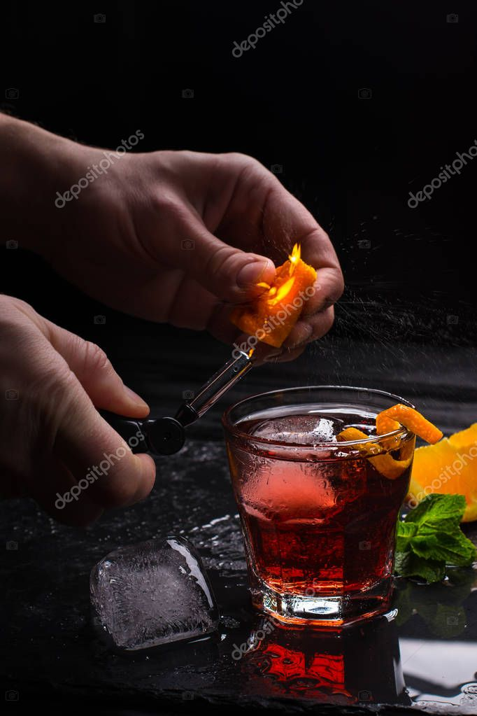 Mezcal Negroni cocktail. Smoky Italian aperitivo. Flamed orange peel.