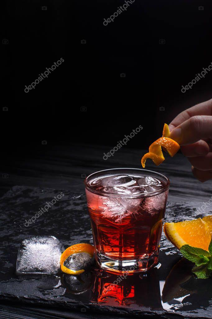 Mezcal Negroni cocktail making. Italian aperitivo. Hand puts orange peel in a cocktail.