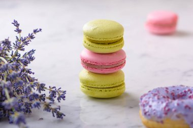 Three macarons and lavender bouquet in center of the image, one lilac donut in front, one pink macaron behind, on white marble table