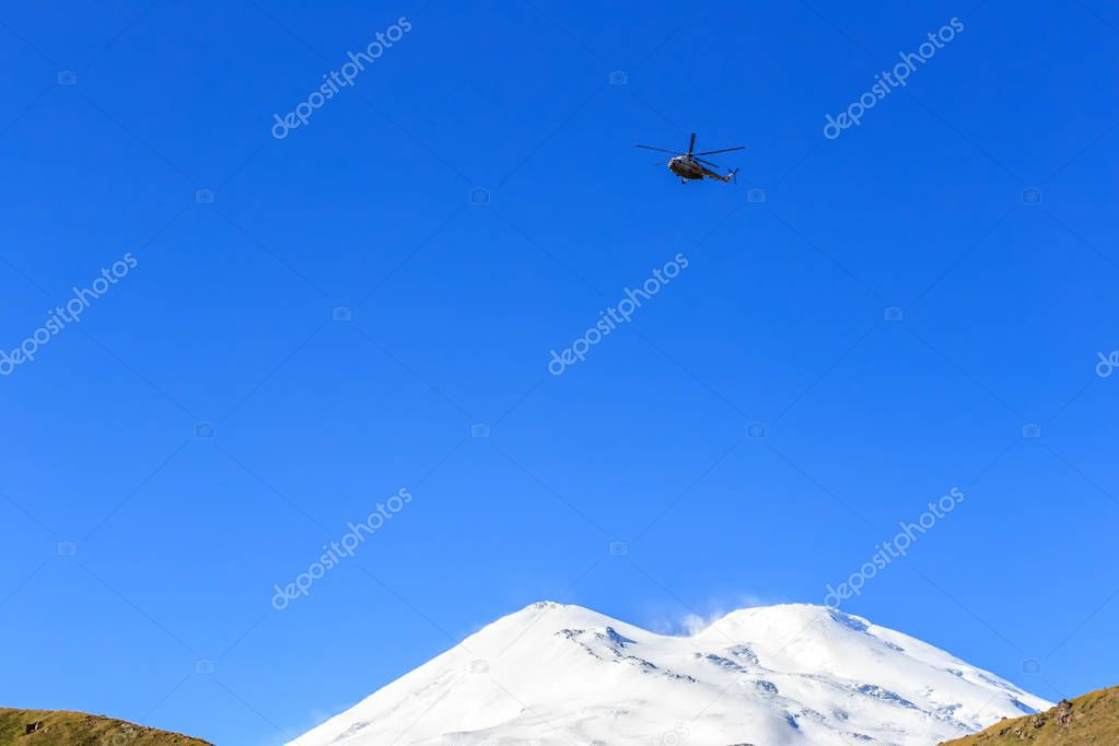 Helicopter on the background of Elbrus peaks