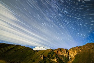 Stars draw fading lines and clouds over Mount Elbrus. Night landscape. Russia. Traces in the form of a line from the stars
