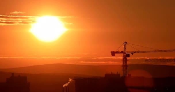 Tower crane against the backdrop of the setting sun. Backlight. Ekaterinburg, Russia. Video. UltraHD (4K)