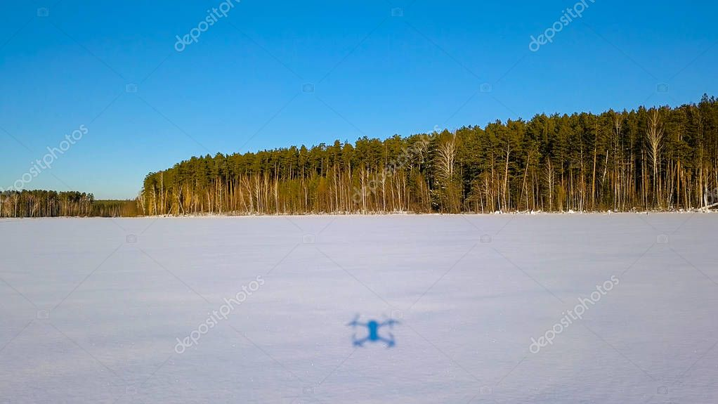 Low flight over the snow with traces. Frozen lake. Shadow from the drone, Maneuvering. Winter clear weather, From Drone