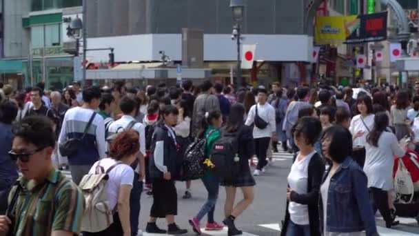 Tokyo, Japan - May 4, 2019 : Close up pedestrians walking on Shibuya Crossing in day time ( Slow Motion Video ). Camera panning left to right, selective focus