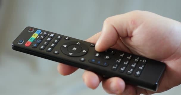 Zavřít až mans ruka držící Tv dálkové ovládání a přepínání Tv kanálů