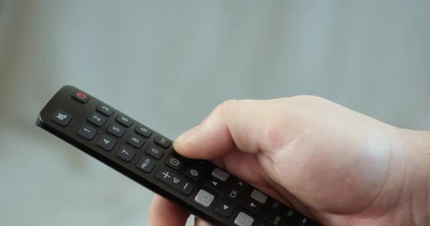 Close up mans hand holding TV remote control and changing TV channels
