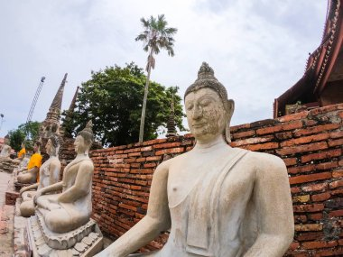 Row of white cement buddha statue with sunlight at Wat Yai Chai Mongkol, Phra Nakhon Si Ayutthaya, Thailand. Beautiful of historic city at buddhism temple.