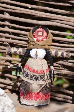 motanka, Ukrainian ethnic traditional toy, handmade textile rag doll, folk craft souvenir, shawl, embroidery, brown canvas, standing at willow palisade in bright sunshine