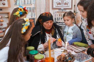 Vinnytsia, Ukraine - 19.03.2018: old woman pysankar teaches little girls to write a floral folk ornament on Easter egg pysanka at ethnographic master class