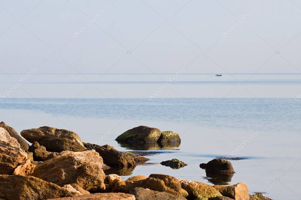 sea beach, stones in water covered with green algae, still blue surface with no waves, beautiful relaxing tourist background, small motorboat near horizon
