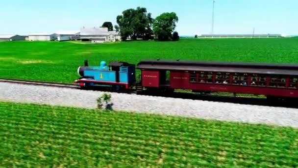 Strasburg, Pennsylvania, June 2018 - Aerial View of Thomas the Train Steam Engine Puffing Along in Amish Farmlands as seen by Drone