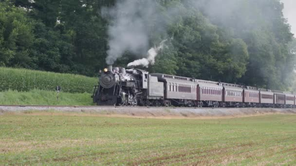 Lancaster, Pennsylvania, July 2019 - Steam Passenger Train Puffing Black Smoke Along Amish Countryside on a Sunny Summer Day
