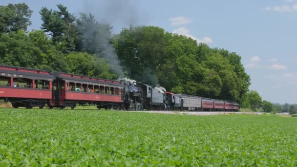 Ronks, Pennsylvania, July 2019 - A 1910 Steam Engine with Passenger Train Pulling into a Station Puffing Black Smoke Along the Amish Countryside as a Second Steam Locomotive Passes on a Sunny Summer Day