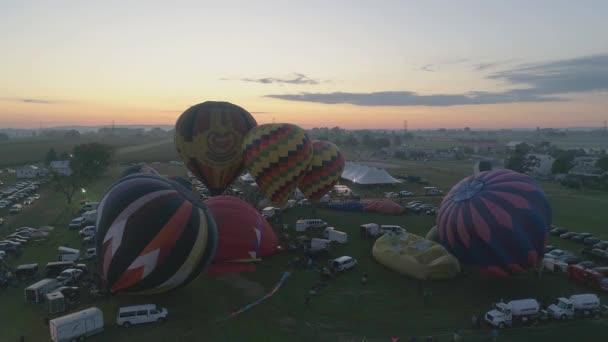Luftaufnahme eines bei Sonnenaufgang startenden Heißluftballons bei einem Ballonfestival an einem klaren Sommermorgen