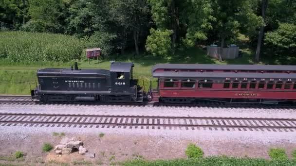 Lancaster, Pensylvánie, červenec 2019-letecký pohled na dieselovou lokomotivu s taháním osobních automobilů přes Amish venkov