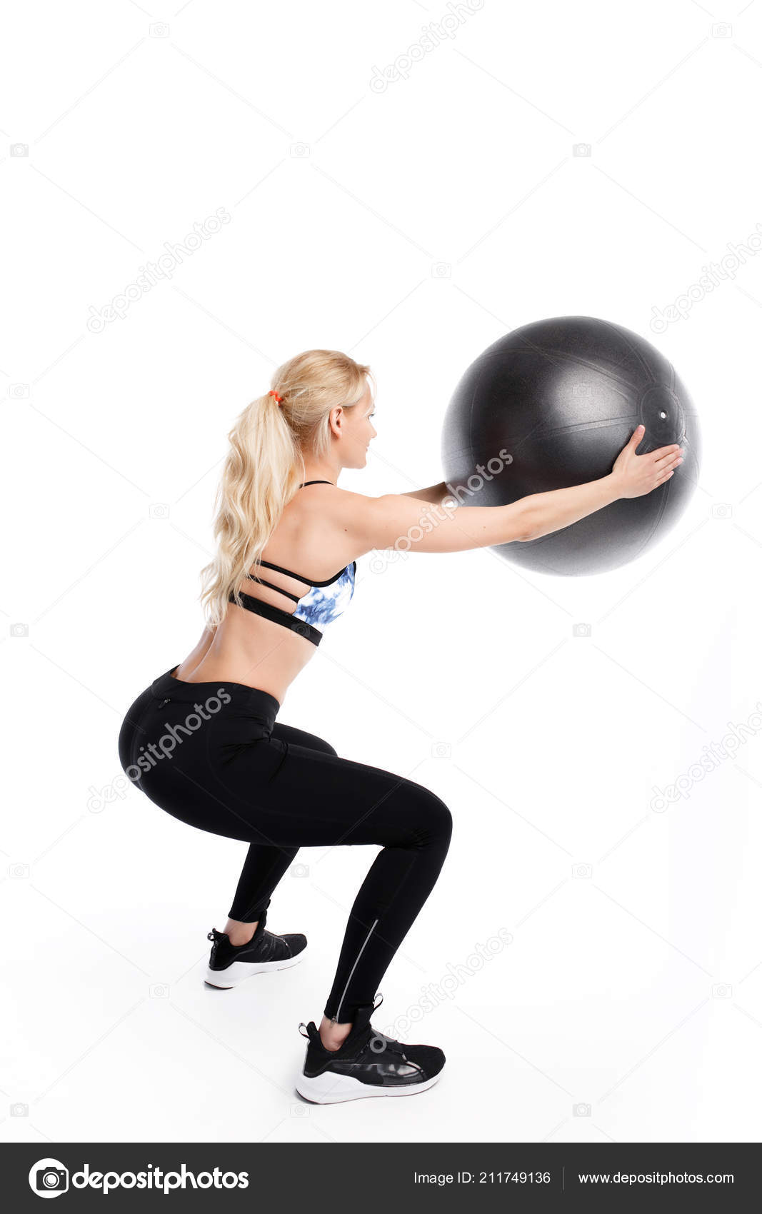 Fit young pretty woman doing squats exercises with fitness ball